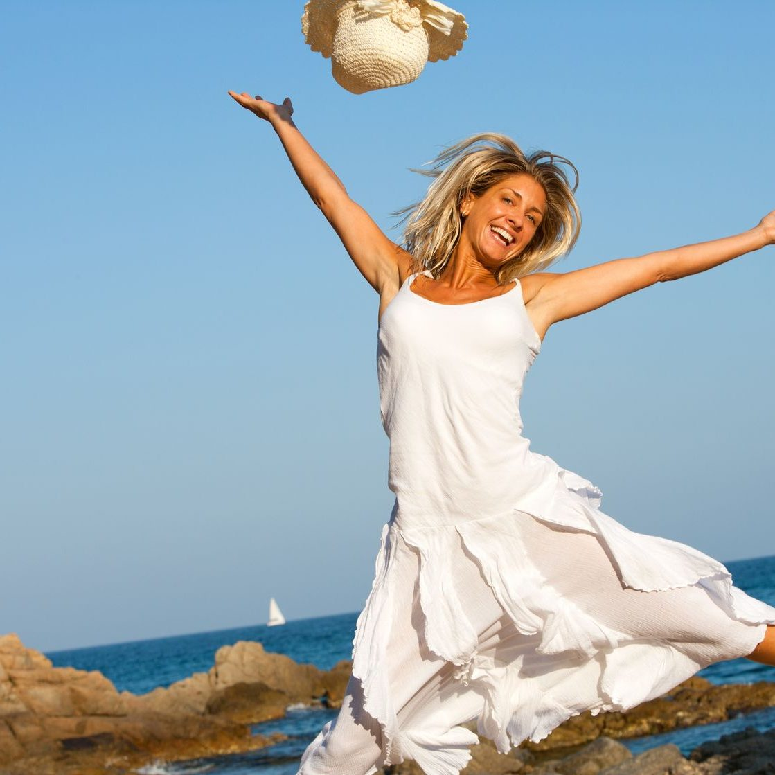 14260581 - happy young woman in white dress jumping on beach